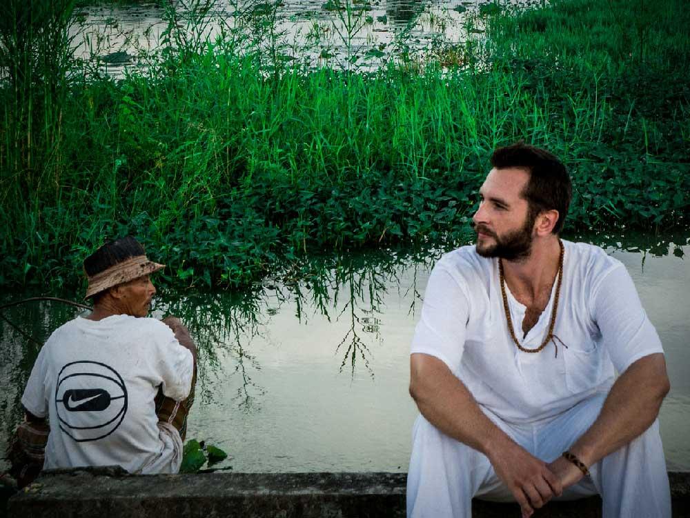 Vipassana-Meditation: Als buddhistischer Moench in weisser Kluft gekleidet sitze ich am See des Klosters in Thailand / Chom Thong.